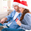 Stock Photo: Couple with credit card buying online. Christmas Shopping