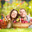Couple Relaxing on the Grass and Eating Apples in Autumn Garden — Stock Photo #14134405