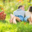 Couple Relaxing on the Grass and Eating Apples in Autumn Garden — 图库照片
