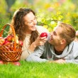 Couple Relaxing on the Grass and Eating Apples in Autumn Garden — ストック写真