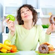 Diet. Beautiful Young Woman choosing between Fruits and Sweets  — Foto Stock