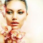 όμορφη κοπέλα με orchid λουλούδια. γυναίκα πρόσωπο ομορφιάς — Φωτογραφία Αρχείου