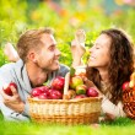 par avkopplande på gräset och äta äpplen i höst trädgård — Stockfoto