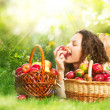 Beautiful Girl Eating Organic Apple in the Orchard - Stock Photo