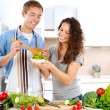 Young Man Cooking. Happy Couple Eating Fresh Vegetable Salad  — Stok fotoğraf