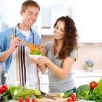 Молодой человек приготовления пищи. Счастливая пара, едят салат из свежих овощей — Стоковое фото