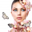 Foto Stock: Beautiful Girl With Orchid Flowers and Butterfly