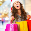 Stock Photo: Christmas Shopping. Woman with Bags in Shopping Mall. Sales