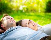 Parku. mladý pár, ležící na trávě venkovní — Stock fotografie