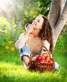 Gelukkig lachende jonge vrouw eten van biologische appel in de boomgaard — Stockfoto