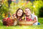 Paar ontspannen op het gras en appels eten in herfst tuin — Stockfoto