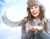 Boże narodzenie dziewczyna. kobieta dmuchanie śniegu — Zdjęcie stockowe