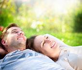 Mladý pár, ležící na trávě venkovní — Stock fotografie