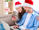 Young couple with laptop and credit card buying online — Stock Photo