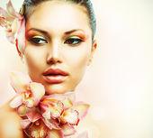 Hermosa chica con orquídeas flores. cara de una mujer de belleza — Foto de Stock
