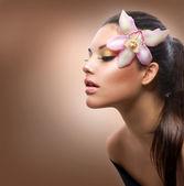 πορτραίτο της ομορφιάς. όμορφο κομψό κορίτσι με ορχιδέα λουλούδι — Φωτογραφία Αρχείου