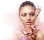 Schönes mädchen mit orchidee blüht. perfektes make-up — Stockfoto