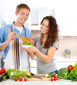 Young Man Cooking. Happy Couple Eating Fresh Vegetable Salad — Stock Photo