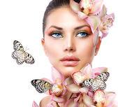 Vacker flicka med orkidé blommor och fjäril — Stockfoto