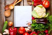 Abra o notebook e o fundo de legumes frescos. dieta — Foto Stock