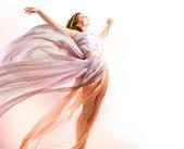 Mooi meisje in waait jurk vliegen — Stockfoto