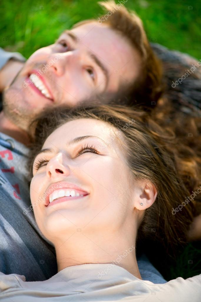 Young Couple Lying on Grass Outdoor — Stock Photo #14134320