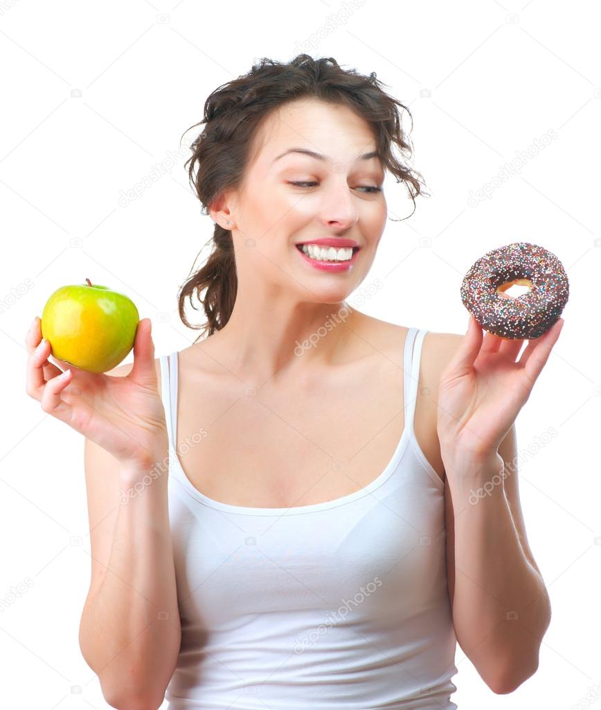 Diet. Beautiful Young Woman choosing between Fruit and Donut  — Stock Photo #14134402