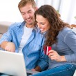 Young couple with Laptop and Credit Card buying online — Foto de stock #16276151