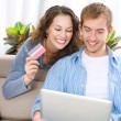 Young couple with Laptop and Credit Card buying online — Stock Photo #16276203