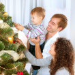 Young Family decorating a Christmas Tree — ストック写真