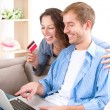 Young couple with Laptop and Credit Card buying online — Stock Photo #16276219