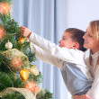 Kids Decorating Christmas Tree. Happy Children - Stock Photo