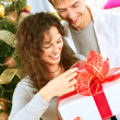 Stock Photo: Happy Couple Opening Christmas Gift. Christmas Family