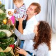 Happy Family Decorating Christmas Tree together - Stock Photo