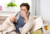 Mujer enferma con termómetro. gripe. estornudar en tejido — Foto de Stock