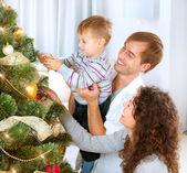 νεαρή οικογένεια διακόσμησης ενός χριστουγεννιάτικου δέντρου — Φωτογραφία Αρχείου