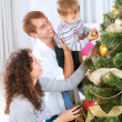 Young Family decorating a Christmas Tree — 图库照片