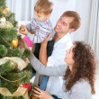 Young Family decorating a Christmas Tree	 — Стоковое фото #19734663