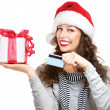 Foto de Stock  : Christmas. Happy Smiling Woman with Gift Box and Credit Card