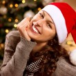图库照片: Christmas Woman in Santa Hat. Happy Smiling Girl