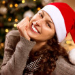 Stock fotografie: Christmas Woman in Santa Hat. Happy Smiling Girl