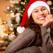 Foto Stock: Christmas Woman in Santa Hat. Happy Smiling Girl