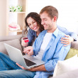 Young couple with Laptop and Credit Card buying online - Stock Photo