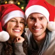 图库照片: Christmas. Happy Couple at home celebrating Christmas