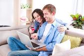 νεαρό ζευγάρι με laptop και πιστωτική κάρτα αγοράζουν σε απευθείας σύνδεση — Φωτογραφία Αρχείου