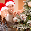 图库照片: Happy Couple Decorating Christmas Tree in their Home