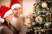 Lyckliga paret dekorera julgran i deras hem — Stockfoto