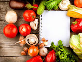 Open Notebook and Fresh Vegetables Background. Diet — Stock Photo