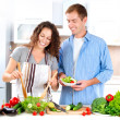 Stock Photo: Young Couple Cooking Vegetable Salad Together
