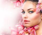 Vacker tjej med orkidé blommor. skönhet kvinna ansikte — Stockfoto